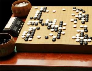 Photo d'un plateau de jeu de Go avec une partie en cours, les pions et une horloge.